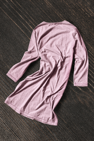 Pink cotton crumpled dress on dark brown wooden background