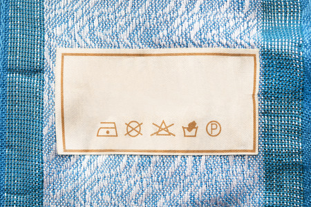 Care clothes label on blue textile background closeup Stockfoto