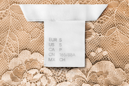 S size clothes label on yellow lacy background closeup