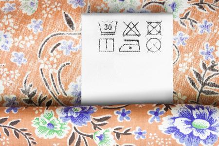Care clothes label on floral orange cotton background closeup Stockfoto