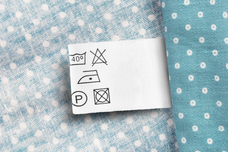 Care clothes label on blue polka dots textile background
