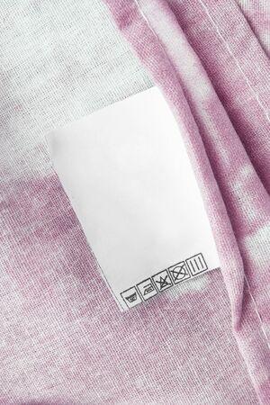 Care clothes label pink cotton background closeup