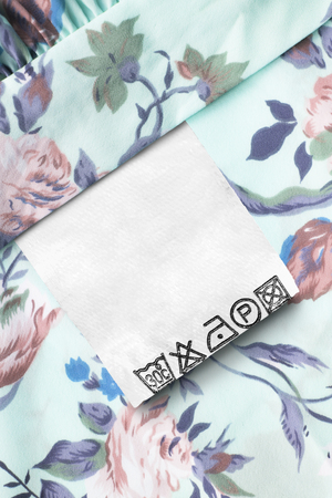 Care clothes label on cyan floral textile background