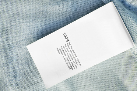 Clothes label says 100% cotton in different languages on blue textile background Stok Fotoğraf