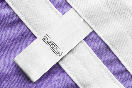 Care clothes label on purple textile background closeup Stockfoto