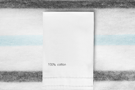 Clothes label says 100% cotton on knitted textile background closeup