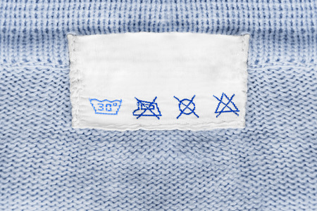 Care clothes label on blue knitted background closeup