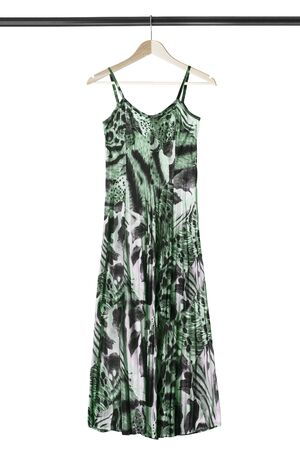 Long green sundress hanging on wooden clothes rack isolated over white