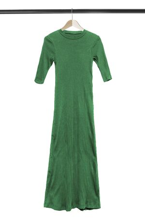 Long green knitted dress on wooden clothes rack isolated over white Stockfoto