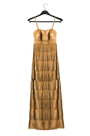 Golden satin fringe gown on black clothes rack isolated over white