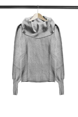 Grey knitted sweater on wooden clothes rack isolated over white Stockfoto