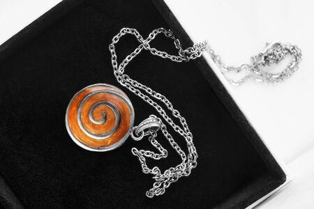 Vintage amber medallion on silver chain in black jewel box Stockfoto