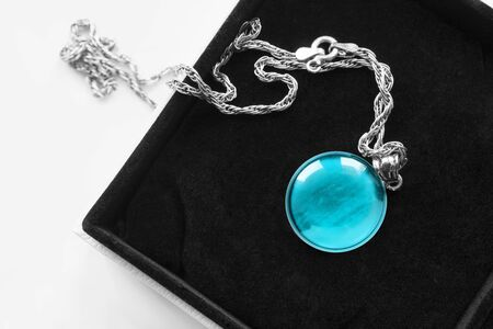 Türkisblaues rundes Medaillon an Silberkette in schwarzer Schmuckschatulle Standard-Bild