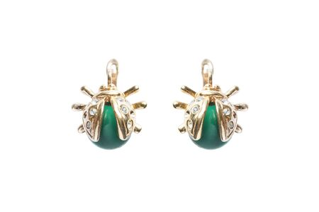 Gold earrings in the shape of bugs with crystals and green gems on white background