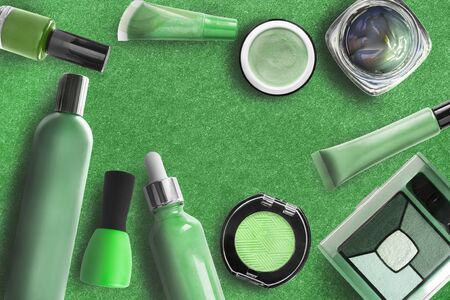 Green cosmetic objects collection on green background