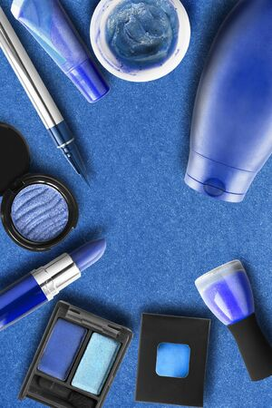 Collection of blue colored cosmetics on blue paper background