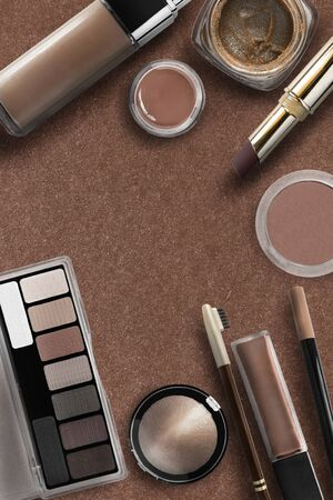 Cosmetic collection in shades of brown on brown background