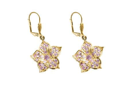 Flower shaped gold earrings with pink crystals isolated over white