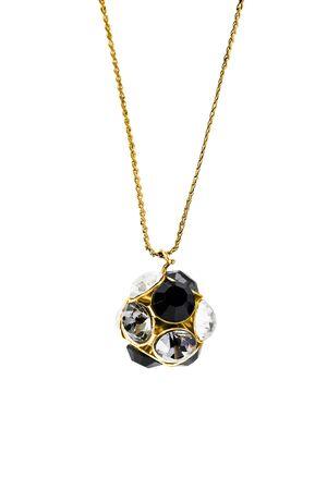 Pendentif en or avec cristaux noirs et blancs suspendus à une chaîne sur fond blanc Banque d'images