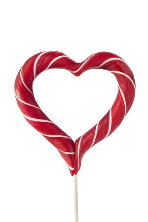 Primer plano de piruleta en forma de corazón rojo sobre fondo blanco.