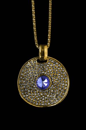 Vintage gold pendant with crystals and one sapphire hanging on a chain on black background Stock Photo