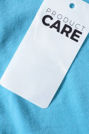 Clothes label says product care on blue cotton background closeup