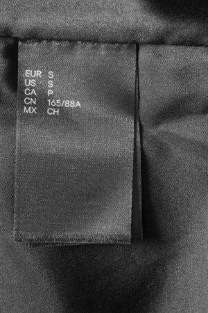 Small size black clothes label on black textile background