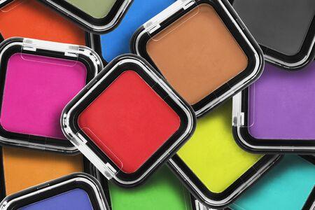 A lot of colorful mat eyeshadows boxes closeup