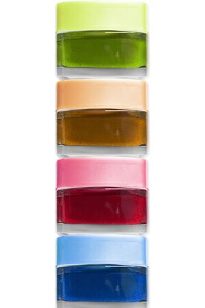 Stack of colorful cosmetic jars on white background Фото со стока