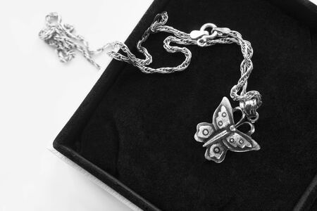 Silver butterfly shaped pendant on a chain in black jewel box