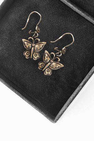Butterfly shaped gold earrings in black jewel box closeup Imagens