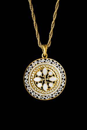 Colgante étnico tallado en oro colgando de una cadena aislada sobre negro Foto de archivo