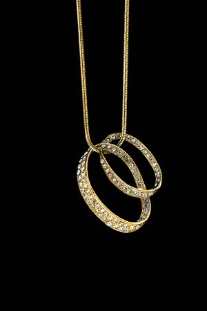 Precious diamond pendant hanging on gold chain on black background
