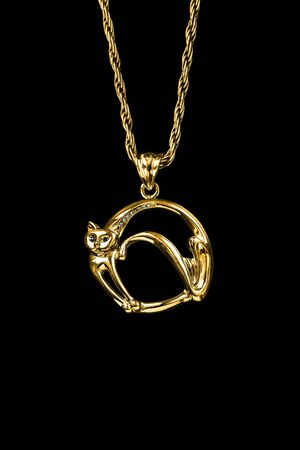Gold pendant in the shape of a cat hanging on a chain isolated over black Reklamní fotografie