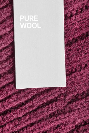 Clothes label says pure wool on knitted maroon background closeup Stok Fotoğraf