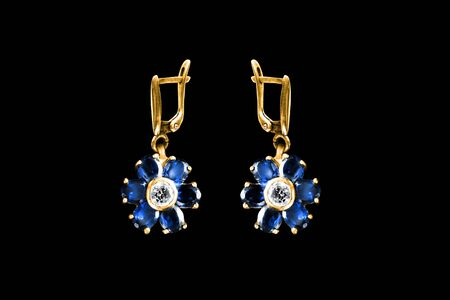 Vintage elegant sapphire earrings in the shape of flowers on black background