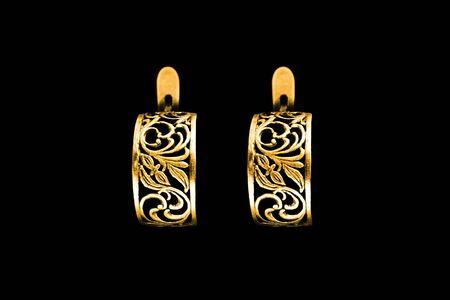 Elegant carved gold earrings on black background