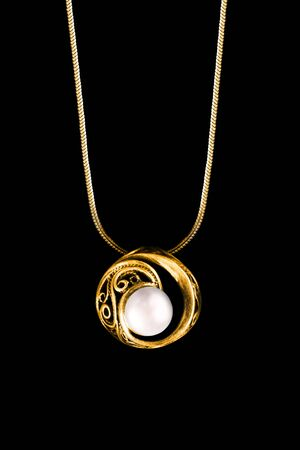 Elegant vintage pearl pendant hanging on gold chain isolated over black