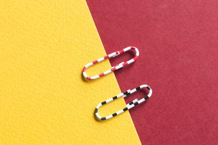 Striped paper clips on yellow and red craft paper sheets 写真素材