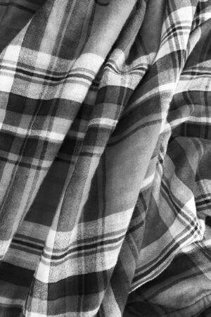Black and white plaid draped cotton closeup as a background