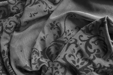 Black embroidered lacy draped fabrics closeup as a background