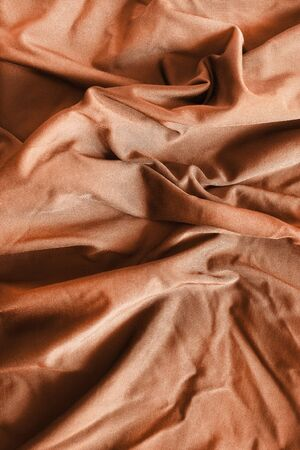 Brown satin crumpled fabrics closeup as a background 写真素材