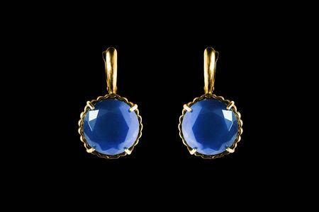 Elegant gold earrings with large blue gems on black background
