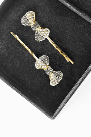 Pair of gold bow shaped hair pins with pearl and crystals in black jewel box closeup