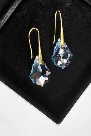 Pair of blue crystal drop earrings in black jewel box closeup Imagens