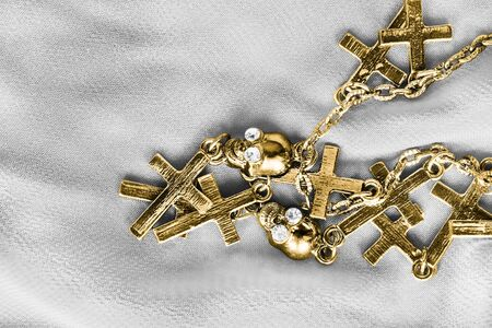 Gold chain with crosses and skulls pendants on white textile background