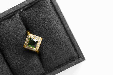 Elegant gold ring with emerald and crystals in black jewel box closeup Standard-Bild