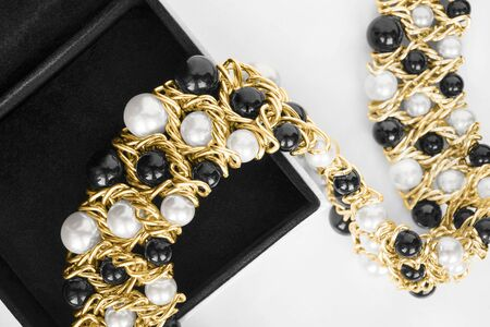 Gold necklace with black and white pearl in black jewel box closeup Imagens