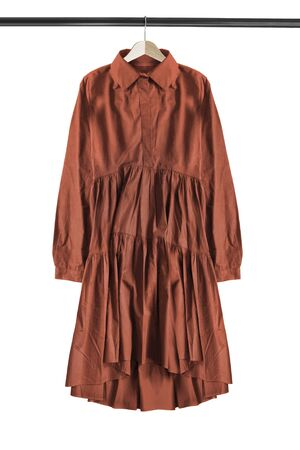 Oversized brown cotton dress hanging on wooden clothes rack isolated over white