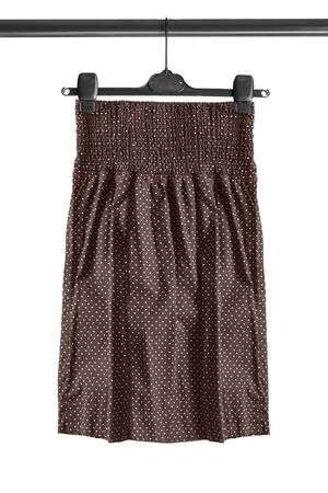 Brown cotton polka dots skirt hanging on clothes rack isolated over white